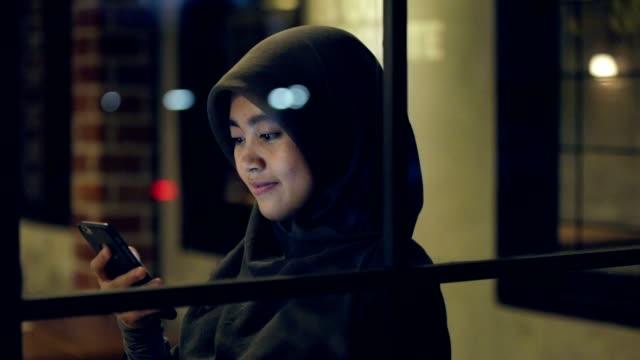 vidéos et rushes de asie du sud-est musulmane avec hijab est l'utilisation et le défilement son smartphone pour naviguer sur internet - indonésie