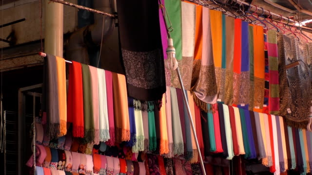 muslim style scarves hanging high in the market - souk video stock e b–roll