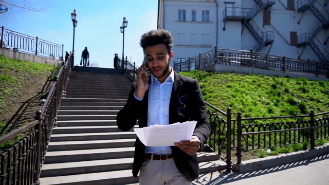Muslim talking about business by phone and putting hands up, slow motion video