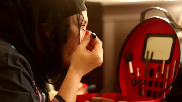 Muslim woman applying  make up Muslim woman applying  make up lip liner stock videos & royalty-free footage