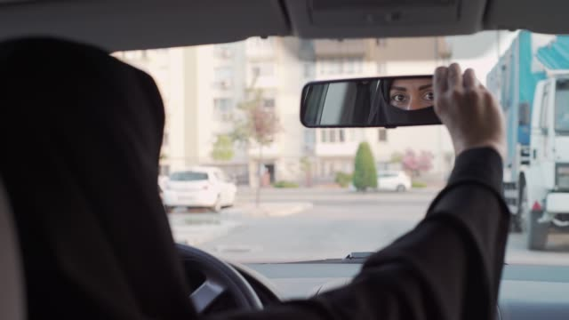 Muslim woman driving a car Muslim woman driving a car. rear view mirror stock videos & royalty-free footage
