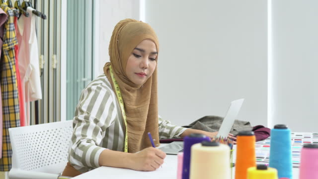 Muslim woman fashion designer work on laptop and sketch on drawing at home studio Muslim woman fashion designer work on laptop and sketch on drawing at home studio fabric swatch stock videos & royalty-free footage