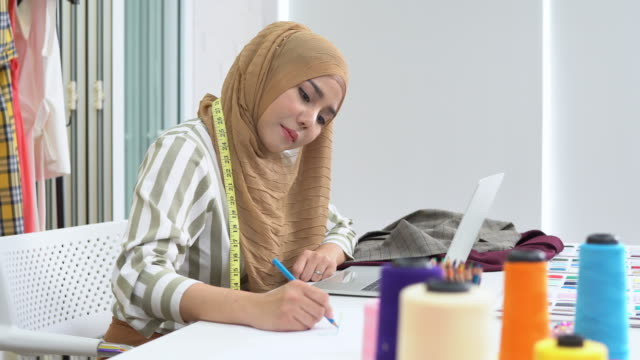 Muslim woman fashion designer work on laptop and sketch on drawing at home studio, Pan shot Muslim woman fashion designer work on laptop and sketch on drawing at home studio, Pan shot fabric swatch stock videos & royalty-free footage