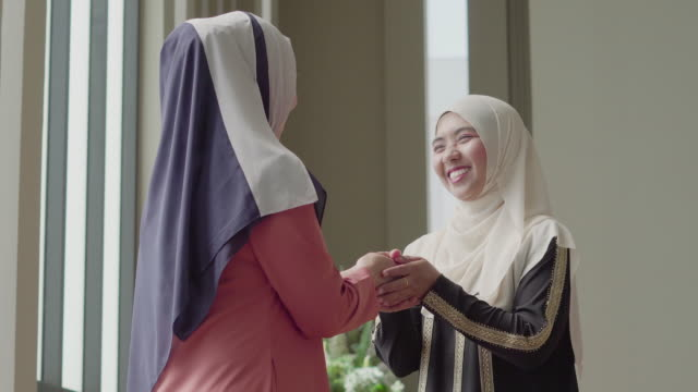 Muslim woman greeting her friend and talking with smile