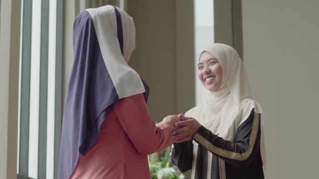 彼女の友人の挨拶と笑顔で話しているイスラム教徒の女性 - インドネシア点の映像素材/bロール
