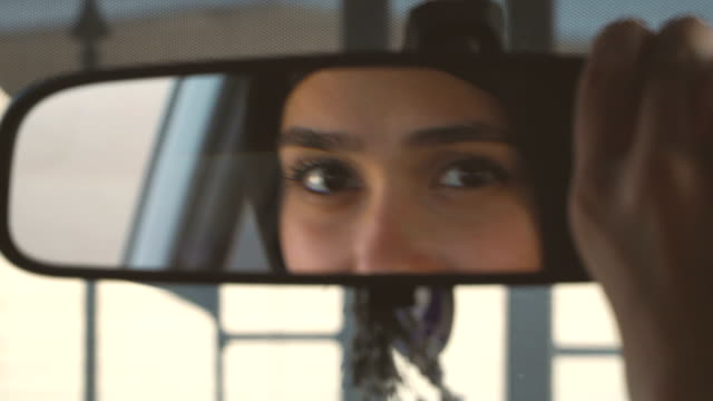 Muslim woman in hijab correcting car rear-view mirror Close up Muslim lady face from rear-view mirror//  4K 3840x2160 / 29.97p / Photo-JPEG / Real Time rear view mirror stock videos & royalty-free footage