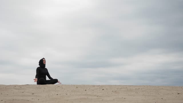muslim woman in hijab exercising healthy lifestyle yoga exercise in desert at sunset - cultura del medio oriente video stock e b–roll