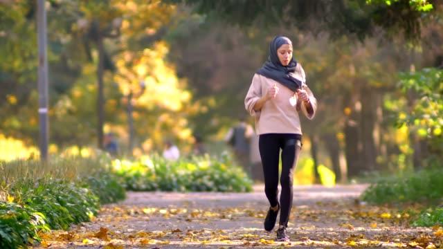 muslimsk kvinna i hijab går jogging i höstlig park, stannar för att kolla klockan och fortsätter att köras - anständig klädsel bildbanksvideor och videomaterial från bakom kulisserna