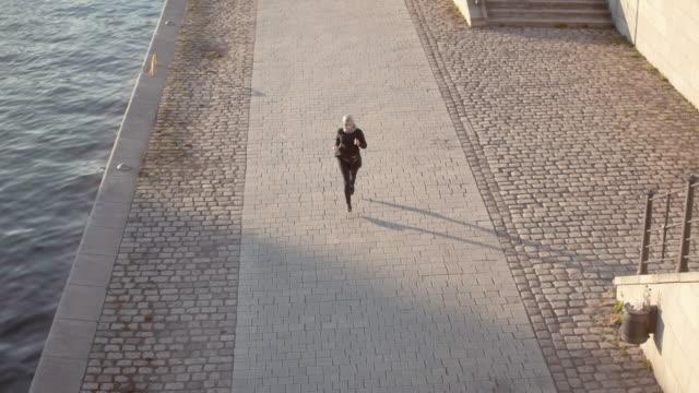 vidéos et rushes de femme musulmane en hijab s'exécutant dans le coucher du soleil (ralenti) - joggeuse