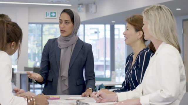 stockvideo's en b-roll-footage met moslimvrouw leidt vergadering - marketing planning