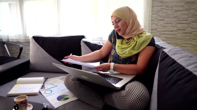 muslim woman looking online for new investment opportunities! - cultura del medio oriente video stock e b–roll
