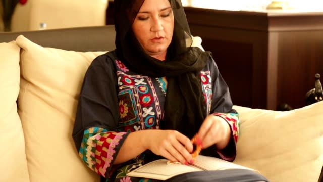 stockvideo's en b-roll-footage met muslim woman praying and reading koran - koran
