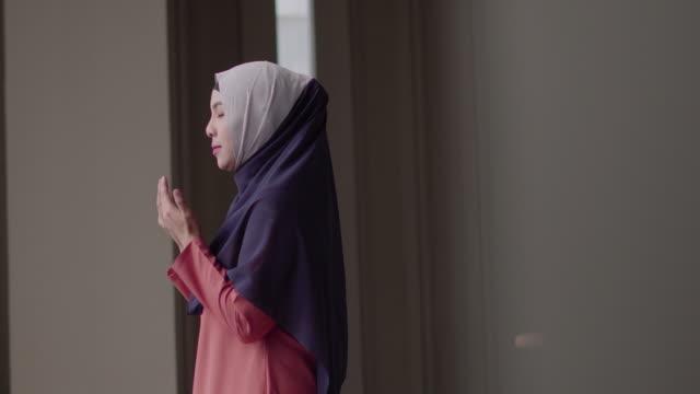 muslim woman praying with copy space. - islam filmów i materiałów b-roll