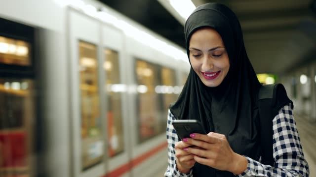 Muslim woman reading text message