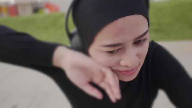 en muslimsk kvinna som vilar efter ett intensivt träningspass på en utomhuspark - hijab bildbanksvideor och videomaterial från bakom kulisserna