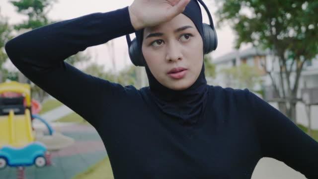 en muslimsk kvinna som vilar efter träningen - hijab bildbanksvideor och videomaterial från bakom kulisserna