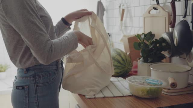 muslimsk kvinna återvänder hem från shoppingresa som transporterar matvaror i plastfria väskor - bära bildbanksvideor och videomaterial från bakom kulisserna