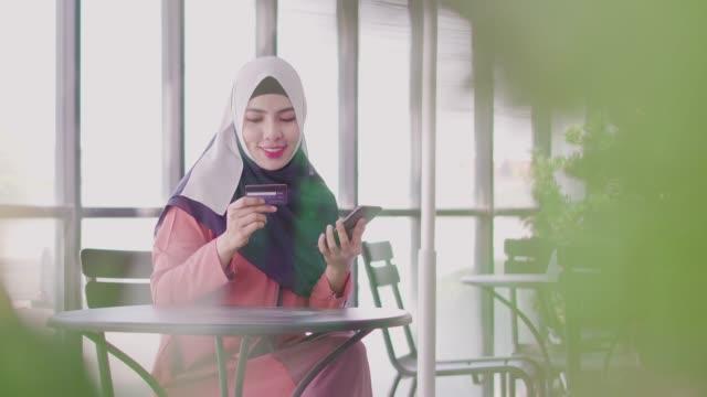 muslimsk kvinna som handlar på nätet med kredit kort och smartphone. - hijab bildbanksvideor och videomaterial från bakom kulisserna