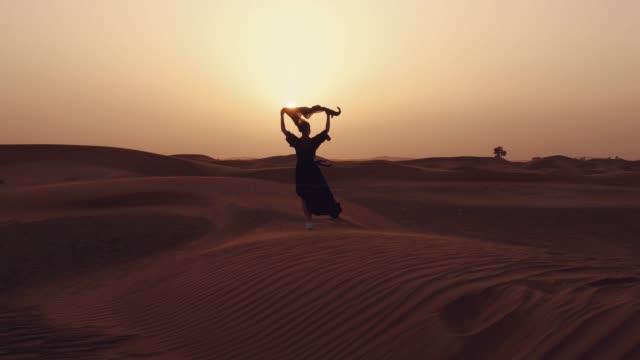 muslimsk kvinna som står nära moskén i öknen. stark vind mellanöstern fred utan krig - pilgrimsfärd bildbanksvideor och videomaterial från bakom kulisserna