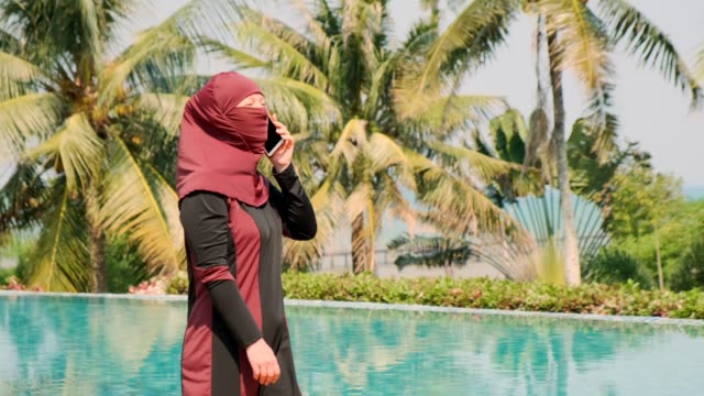 Muslim woman talking on phone while walking near pool on background of tropical trees