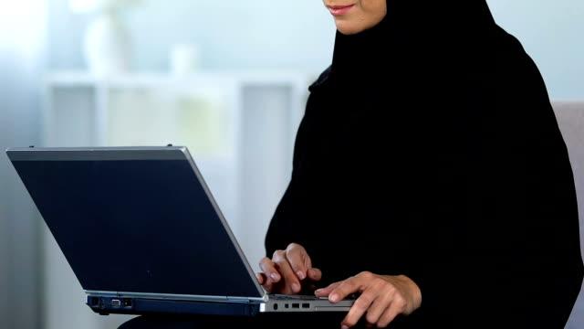 muslimsk kvinna som skriver på bärbar dator, arbetar hemma, frilansande eller utbildning - anständig klädsel bildbanksvideor och videomaterial från bakom kulisserna