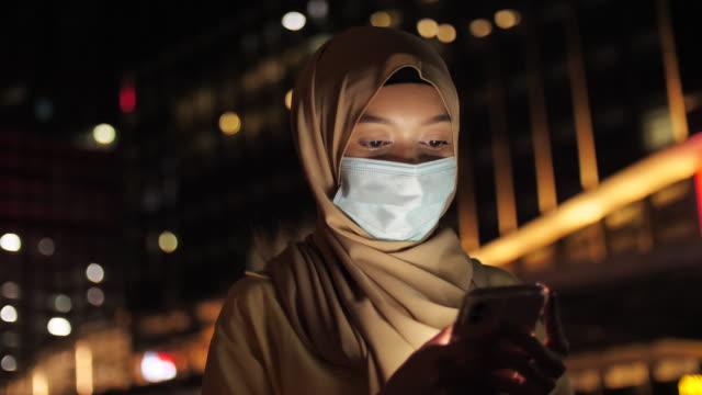 Muslim woman using phone at night