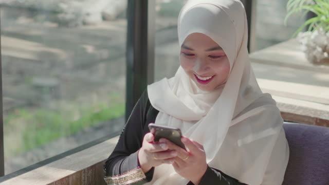 muslimsk kvinna med smartphone för sociala medier. - hijab bildbanksvideor och videomaterial från bakom kulisserna