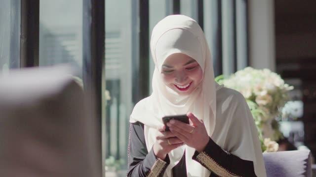 muslimsk kvinna som använder smartphone i coffee shop. - hijab bildbanksvideor och videomaterial från bakom kulisserna