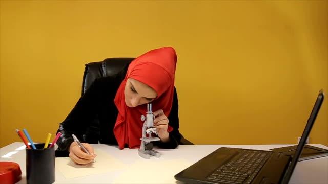 Muslim woman watching through microscope video