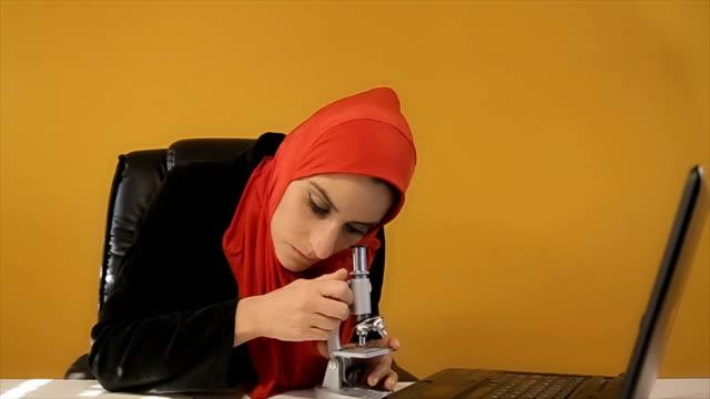 Muslim woman watching through microscope,biologist -professional occupation video