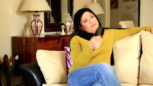 muslimsk kvinna tittar på tv - anständig klädsel bildbanksvideor och videomaterial från bakom kulisserna