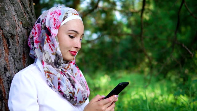 A Muslim woman with a smile is writing on the phone with a friend, in the park video