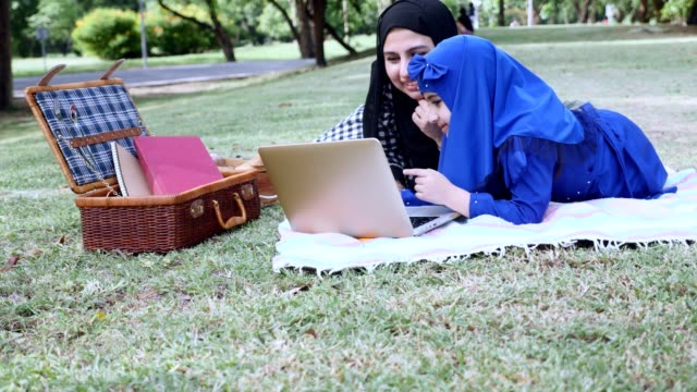 muslim woman with her daughter looking for information on the internet. - abbigliamento modesto video stock e b–roll