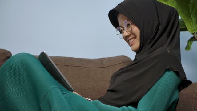 a muslim woman with smiling face, sitting on the sofa in the living room at home watching movies, series from her tablet phone during coronavirus quarantine period - abbigliamento modesto video stock e b–roll