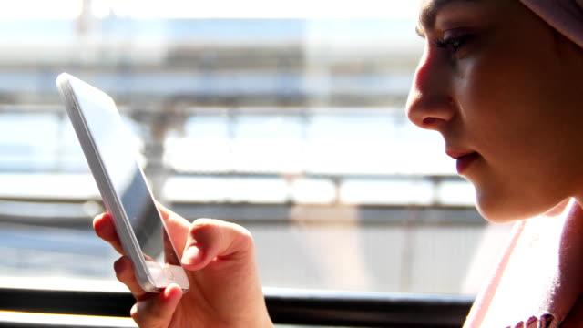 muslimska kvinnor tittar på telefonen, under tågresan - anständig klädsel bildbanksvideor och videomaterial från bakom kulisserna