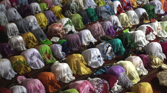 muslim women praying inside istiqlal mosque, jakarta, indonesia - индонезия стоковые видео и кадры b-roll