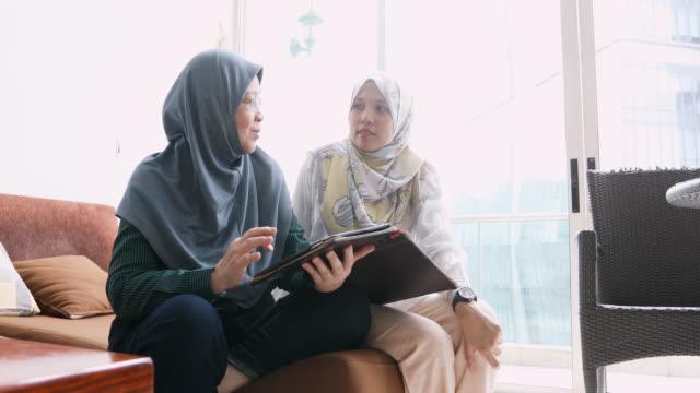 muslimska kvinnor använder en surfplatta tillsammans - anständig klädsel bildbanksvideor och videomaterial från bakom kulisserna