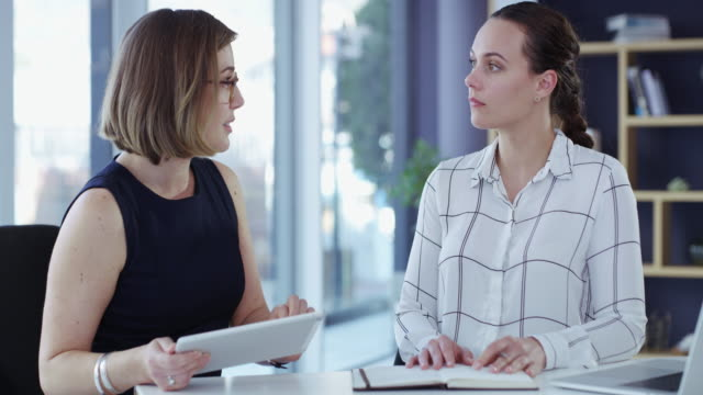 A must have device for a productive meeting 4k video footage of two young businesswomen using a digital tablet in a modern office employee engagement stock videos & royalty-free footage