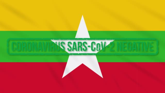 myanmar swaying flag with green stamp of freedom from coronavirus, loop - naypyidaw video stock e b–roll