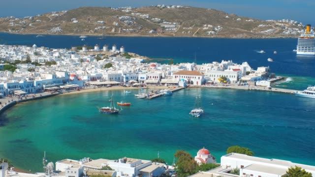 Mykonos island port with boats, Cyclades islands, Greece View of Mykonos town with famous windmills, and port with boats and cruise ship on summer day. Mykonos, Cyclades islands, Greece. With camera panning greek islands stock videos & royalty-free footage