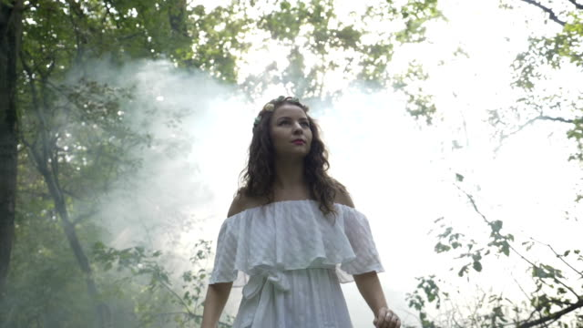 mysterious angelic girl in white dress spinning amongst the trees in the forest - аксессуар для волос стоковые видео и кадры b-roll