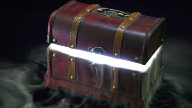 a mysterious atmosphere where light and smoke leaks from a vintage treasure box - scatola del tesoro video stock e b–roll