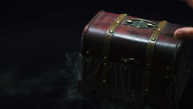 ヴィンテージの宝箱から光と煙が漏れる神秘的な雰囲気 - 骨董品点の映像素材/bロール