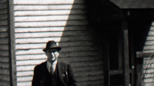 1938: Mysterious federal agent man walking from shady shadows. video