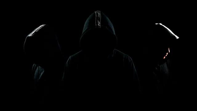 vídeos de stock e filmes b-roll de mysterious hooded man standing in the dark - capuz