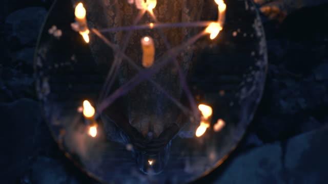 Mysterious pentagram on ritual mirror, reflection of occult magician with candle