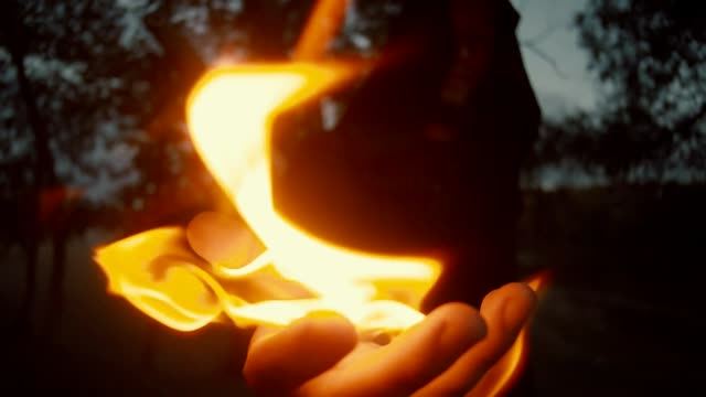 vidéos et rushes de robe de mystérieux sorceleur dans un manteau tenant un homme de feu de fantasy médiévale. halloween - charmeur