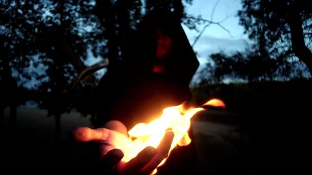 bir ateş adam fantezi olarak ortaçağ tutan bir pelerin içinde gizemli witcher elbise. cadılar bayramı - fantastik stok videoları ve detay görüntü çekimi