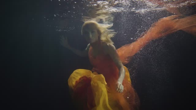 mysterious woman swimming like mermaid under water in on dark background - fata video stock e b–roll