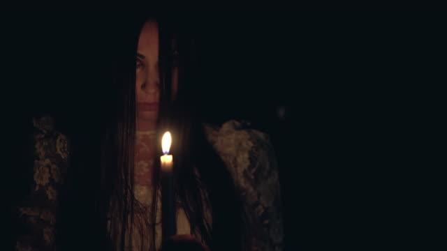 燃えるろうそく、怖いオカルトの儀式で暗闇の中を歩く神秘的な女性 - 不吉点の映像素材/bロール